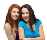 Abbracciare di risata di due ragazze Fotografie Stock Libere da Diritti