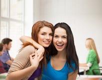 Abbracciare di risata di due ragazze Fotografie Stock