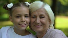 Abbracciare felice della nipote e della nonna, posante per la macchina fotografica, valori familiari archivi video