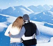 Abbracciare felice delle coppie esterno alle montagne di inverno Fotografie Stock