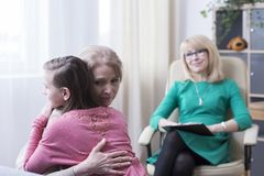 Abbracciare figlia adolescente allo psicologo immagini stock