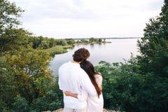 Abbracciare le coppie sui precedenti del fiume vicino al fogliame Fotografie Stock Libere da Diritti