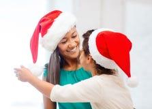 Abbracciare madre e figlia in cappelli dell'assistente di Santa Immagine Stock