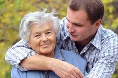 Abbracciare persona anziana immagine stock libera da diritti