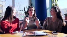 Abbraccio amichevole, amiche felici che parlano nel ristorante che si siede alla tavola video d archivio