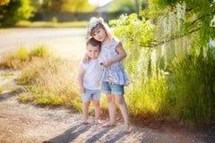 Abbraccio dei bambini contro lo sfondo delle glicine Fotografia Stock Libera da Diritti