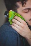 Abbraccio del giovane il suo pappagallo dell'animale domestico sulla spalla Fotografie Stock Libere da Diritti