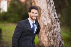 Abbraccio dell'uomo d'affari un tronco di albero fotografia stock libera da diritti