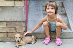 Abbraccio della bambina un cucciolo Fotografia Stock