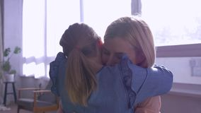 Abbraccio della madre, piccole attività della figlia nelle armi della mamma ed abbraccio di elasticità grande a casa contro la fi