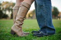 Abbraccio delle gambe delle coppie nel campo di erba. Fotografia Stock
