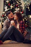 Abbraccio e baci del marito la sua moglie mentre elasticità che il suo Natale presen fotografia stock