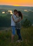 Abbraccio romantico delle coppie al tramonto su paesaggio all'aperto e bello e sul cielo giallo luminoso, concetto di tenerezza d Fotografie Stock