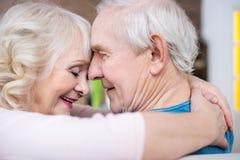 Abbraccio senior delle coppie e fronti commoventi a casa Fotografie Stock Libere da Diritti