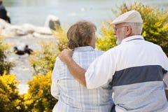 Abbraccio senior delle coppie su un banco nel parco immagine stock