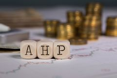 Abbreviation AHP composed of wooden letter. Stacks of coins in the background. Closeup stock photos