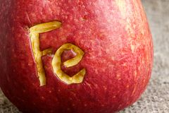 Abbreviation Fe. Scratched on an apple skin. Close up royalty free stock photos