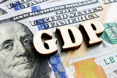 Abbreviation GDP Gross Domestic Product from wooden letters on the dollar bill