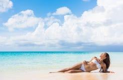 Abbronzatura di rilassamento del sole della spiaggia del bikini della donna sexy del corpo immagine stock