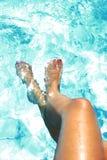 Abbronzi le gambe dorate della giovane donna e dei piedi di chiodi dipinti che hanno abbronzatura alla piscina Immagini Stock