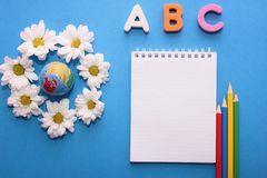 ABC这第一英语字母表的信件在蓝色背景的在小地球和白色菊花旁边 笔记本和 免版税库存照片