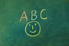 ABC écrit sur un tableau vert, avec un smiley sous photos libres de droits