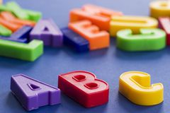 Abc. Plastic colored letters in diagonal with others out of focus in the background Stock Photos