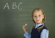 ABC... Little, pretty girl standing in front of blackboard. Holding chalk. Smiling and looking at camera Royalty Free Stock Images
