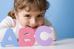 ABC. Happy girl playing with alphabet Royalty Free Stock Photos