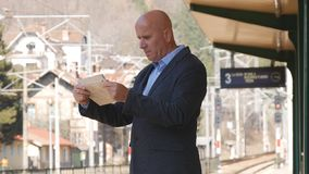Businessman Read Newspaper Waiting a Train in Railway Station royalty free stock photography