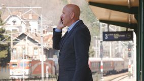 Businessman Talking to Mobile Phone in a Train Station stock images