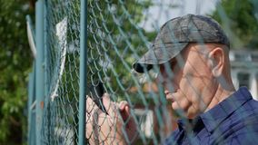 Man Near a Metallic Fence Text Using a Smartphone. stock photo