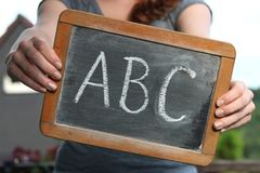 ABC. Written with chalk on slate shown by young female stock images