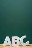 Abc-alfabetet märker framme av bräde Arkivbild
