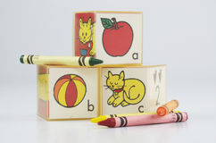 ABC Blocks Of Plastic And Crayons. Preschool blocks with ABC and an apple, ball, and cat, plus green,orange,yellow and red crayons Royalty Free Stock Photo