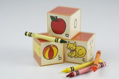 ABC Blocks Of Plastic And Crayons. Preschool blocks with ABC and an apple, ball, and cat, plus green,orange,yellow and red crayons Royalty Free Stock Image