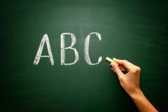 Abc-bokstäver med handen och krita på svart tavla Arkivbilder