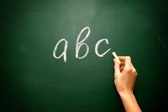 Abc-bokstäver och krita med kvinnahanden Arkivbild