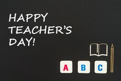 Abc-bokstäver och träflismaterialminiatyr på svart tavla med för lärare` s för text lycklig dag Arkivfoto
