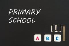 Abc-bokstäver och träflismaterialminiatyr på svart tavla med textgrundskola för barn mellan 5 och 11 år Royaltyfri Foto