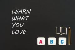 Abc-bokstäver och träflismaterialminiatyren på svart tavla med text lär vad du älskar Royaltyfri Fotografi