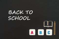 ABC-Buchstaben und Spanplattenminiatur auf Tafel mit Text zurück zu Schule lizenzfreie stockbilder