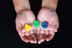 ABC in child hands. ABC in child's hands on black background stock images