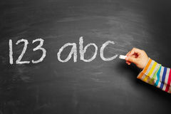 123 abc. Child's hand writing 123 abc! on blackboard Royalty Free Stock Photography