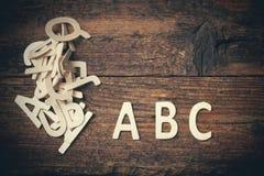 ABC de madera pone letras a alfabeto en el fondo de madera Imagenes de archivo