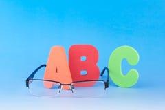ABC and eyeglasses. Colourful ABC and eyeglasses on blue background Stock Photos