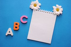 ABC-the first letters of the English alphabet on a blue background. Notebook and white chrysanthemum . Empty space for text. Learn. ABC-the first letters of the royalty free stock photography