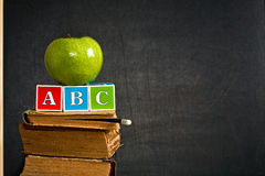 ABC and green apple on old textbook. Against blackboard in class. School concept Stock Images