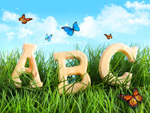 ABC letters in the grass. With butterflies royalty free stock photography