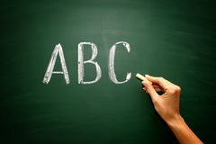 Abc letters with hand and chalk on blackboard Stock Images